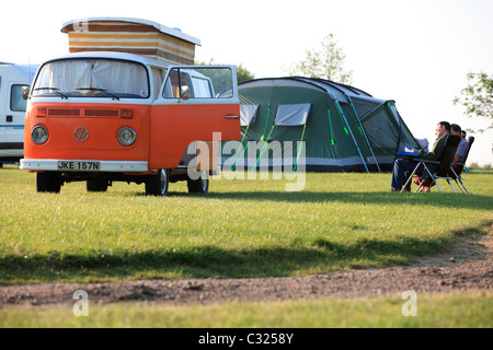 Couple sitting by tent and Volkswagen W camper van in a field in the morning light camping in East Sussex - Stock Photo