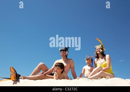 Portrait of modern family sitting on sandy beach against blue sky - Stock Photo