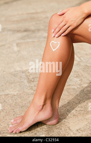Woman with heart shape of lotion on her leg - Stock Photo