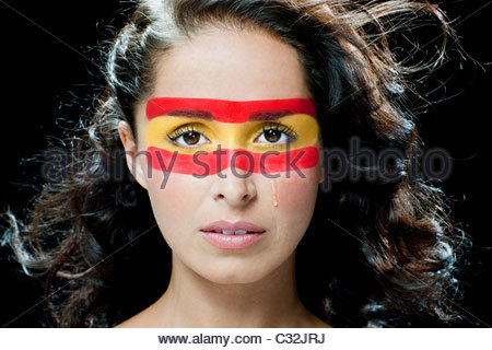 Woman with Spanish flag painted on face - Stock Photo