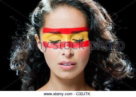 Woman with Spanish flag painted on face, crying - Stock Photo