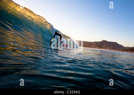 A surfer riding a red surfboard sets up for a barrel while surfing at Zuma Beach in Malibu, California. - Stock Photo