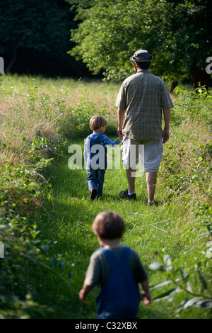 Four-year-old boy walks with father in field. - Stock Photo