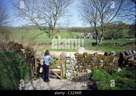 Female operating a metal lever opening a wooden gate on a footpath leading onto the Monsal Trail at Hassop - Stock Photo