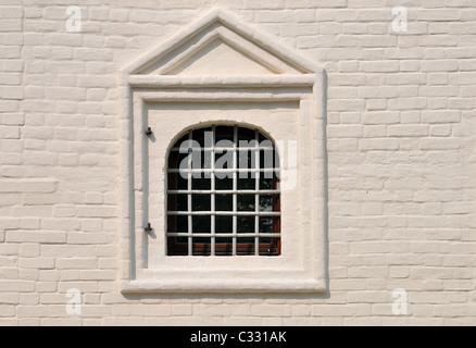 Stucco whitewash old brickwork wall and window with iron bar - Stock Photo