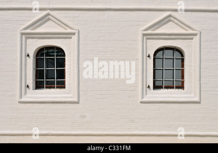 Stucco whitewash old brickwork wall and windows with iron bar - Stock Photo