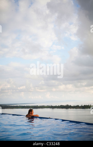 A woman sits with her arms on the edge of an infinity pool overlooking the wide open ocean. - Stock Photo
