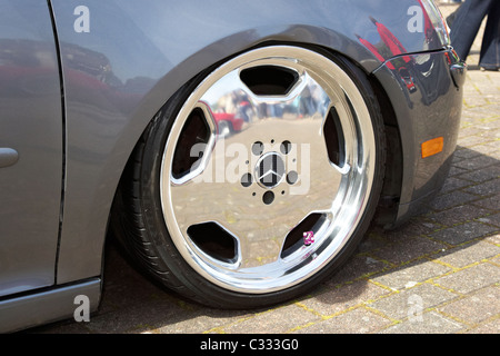 chrome mercedes wheel on a lowered suspension volkswagen golf with resultant wing damage at a modified car show - Stock Photo