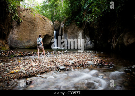 A woman stands at the edge of a pool of water looking at a waterfall while wearing a backpack. - Stock Photo
