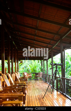 A porch with a set of chairs and a pair of binoculars overlooking the jungle. - Stock Photo