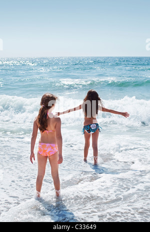 Two young girls playing in the waves at Torrance Beach in Los Angeles, California. - Stock Photo
