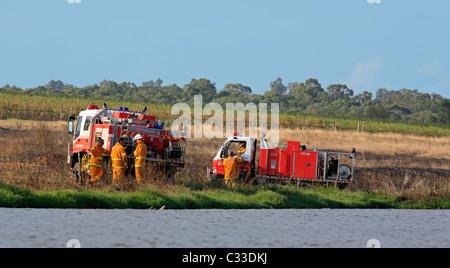 Volunteer Firefighters at their fire trucks after attending a grass fire. Pokolbin, Hunter Valley, NSW, Australia. - Stock Photo