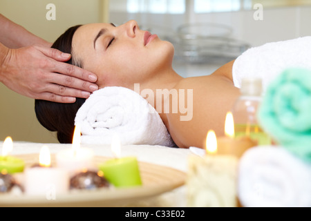 Portrait of young female enjoying the procedure of facial massage - Stock Photo
