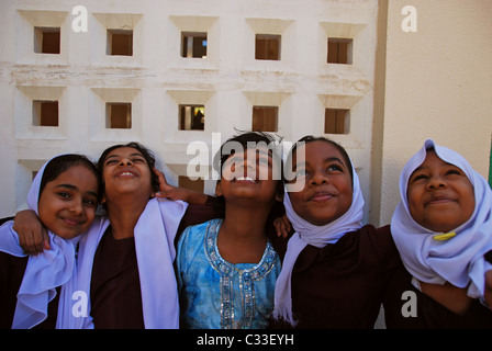 Oman, Muscat, close-up of happy five school girls with arms around in a traditional uniform - Stock Photo
