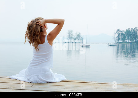 Rear view of pretty young lady in white cotton clothes having rest by the seaside - Stock Photo