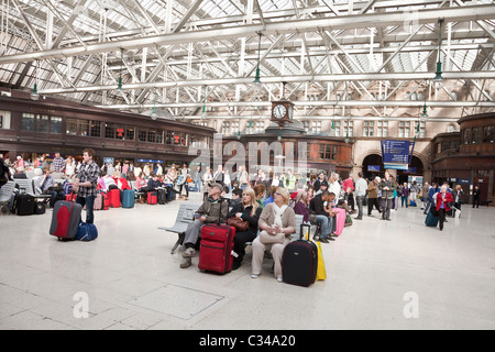 Passengers waiting for trains in the concourse at Glasgow Central Station. - Stock Photo