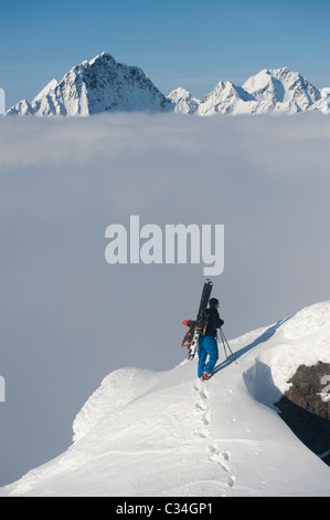 Free skier on top of a mountain admiring the wintery mountain landscape in Lyngen, Norway. - Stock Photo