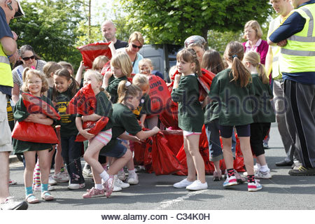 Girls collecting coal sacks in preparation for their coal race . Gawthorpe World Coal Carrying Championships West - Stock Photo