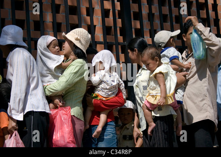 Men and women are waiting in a line with their children for free medical treatment at the Bopha Hospital in Phnom - Stock Photo