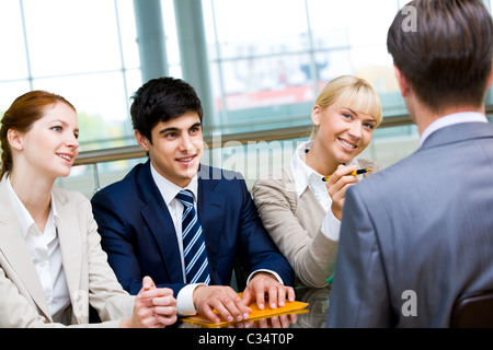 Friendly group of specialists speaking to businessman during interview - Stock Photo