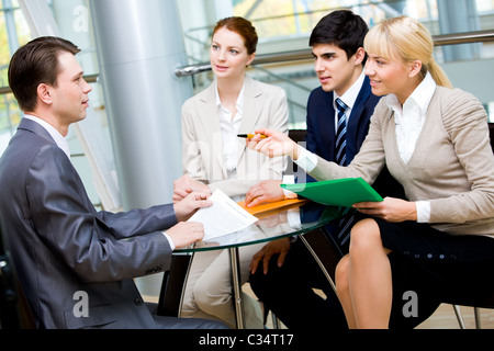 Friendly group of specialists speaking to businessman during negotiations - Stock Photo