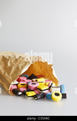 Liquorice allsorts spilling out of a brown paper bag.  Pale grey background. - Stock Photo