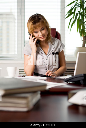 Portrait of executive woman talking on the phone with client of corporation where she works - Stock Photo