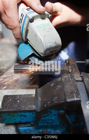 A person uses an angle grinder on metal held in a vice - Stock Photo