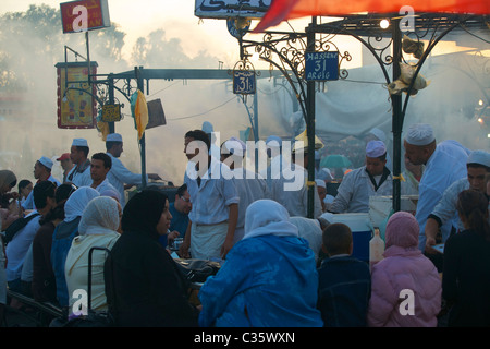 Bustling food stall in the main square, Marrakech, at dusk. - Stock Photo