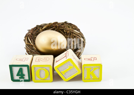 Gold nest egg sits behind alphabet blocks spelling 401K in a concept image of saving for retirement and future goals. - Stock Photo