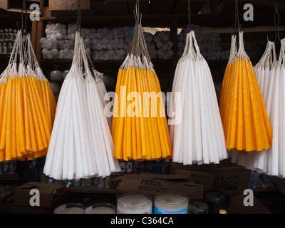Traditional candles used to light and honor ancestors hang for sale in a market stall in the public market in Chichicastenango. - Stock Photo