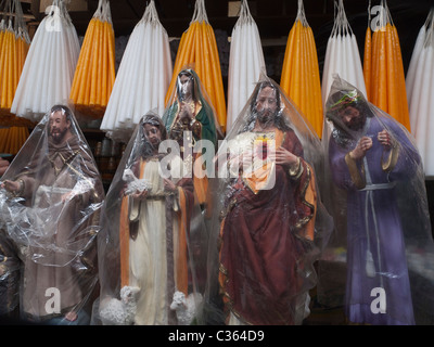 Small religious Catholic statues stand for sale covered in clear plastic in front of rows of candles in the public - Stock Photo