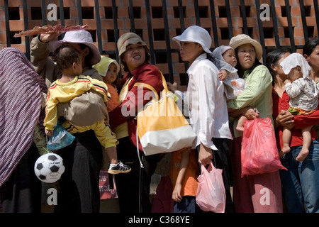 Women are waiting in a ine with their children for free medical treatment at the Bopha Hospital in Phnom Penh, Cambodia. - Stock Photo