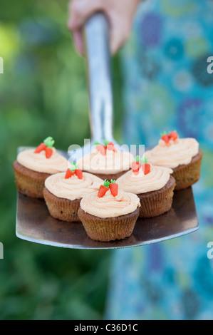 Carrot cupcakes on garden spade selective focus - Stock Photo