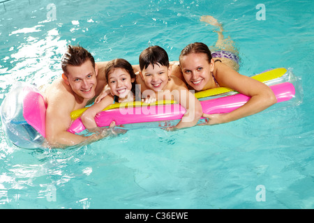 Cheerful family in swimming pool having nice time - Stock Photo