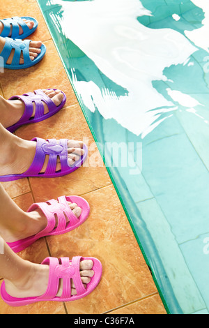 Three pairs of feet in flipflops in swimming pool - Stock Photo