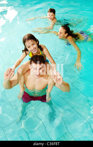 Photo of happy girl sitting on her father shoulders in pool with swimming boy and mother on background - Stock Photo