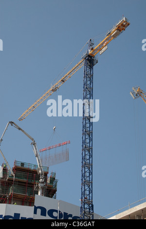 Tower crane lifting a prefabricated reinforcement bar cage used for concrete frame construction in Stratford, East - Stock Photo
