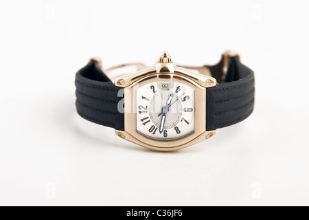 front view of black strap and gold watch - Stock Photo
