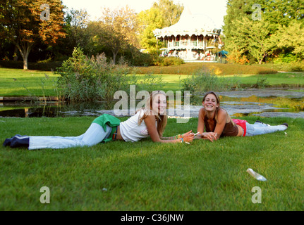 Teenage girls in grass plot at amusement park smoking cigarettes and looking at the camera while lying in the grass - Stock Photo