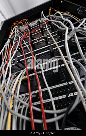 Low angle shot of network switch full of ethernet cables in server room - Stock Photo