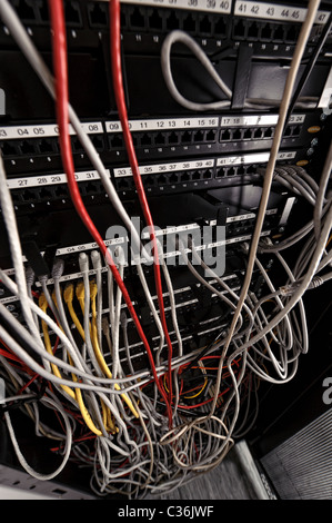 Network switch full of ethernet cables in server room - Stock Photo