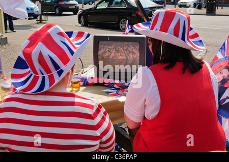 Two women sitting outside, watch the Royal Wedding on a small portable televison - Stock Photo