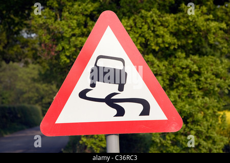 Red triangle road sign for risk of skidding - Stock Photo