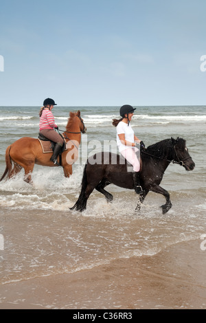 Horse riding teenagers; Two girls riding their horses on Holkham beach,  Norfolk, UK - Stock Photo
