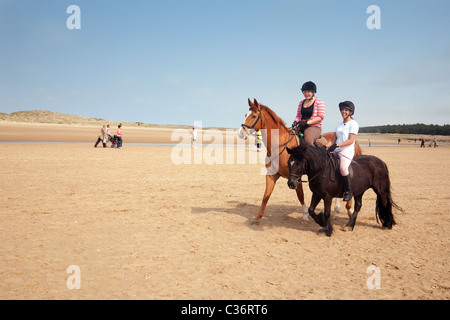 Two girls riding their horses on Holkham beach, North Norfolk, UK - Stock Photo