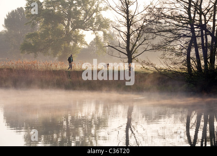 Man walking the dog in countryside at dawn on a spring morning, the river Thames at  Wallingford, Oxfordshire, UK - Stock Photo