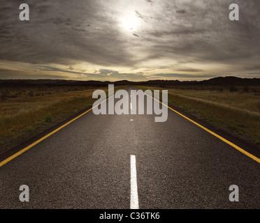 Straight tar road leading into the light (toned image) - Stock Photo
