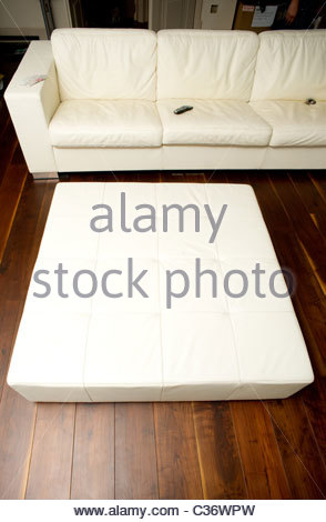 Varnished wooden floor in a central London home - white leather couch sofa empty room interior - Stock Photo