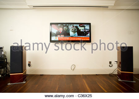 Varnished wooden floor in a central London home with large screen TV attached to wall living room TV stereo speakers - Stock Photo